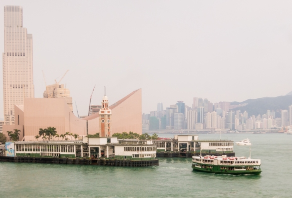 A Star Ferry boat docking in the Kowloon ferry terminal, with the Hong Kong Museum of Art and the Clock Tower in the background, Hong Kong, S.A.R., People_s Republic of China; the ferr
