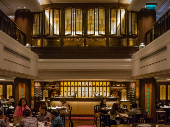 Beautiful Art Deco era woodwork and stained glass decorate the dining room of the Spring Moon Cantonese Restaurant in the Peninsula Hotel, Hong Kong, S.A.R., People_s Republic of China