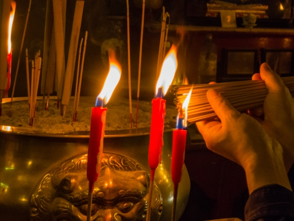 Lighting incense sticks for an offering in the Man Mo Temple, Hong Kong, S.A.R., People_s Republic of China