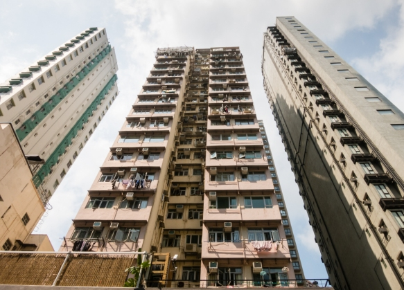 Older highrise apartment buildings soar above the retail shops in the Sheung Wan District of Hong Kong (Island), S.A.R., People_s Republic of China, the area where the British first cl