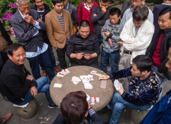 One of many card games underway with numerous spectators in People_s Park, Shanghai, China