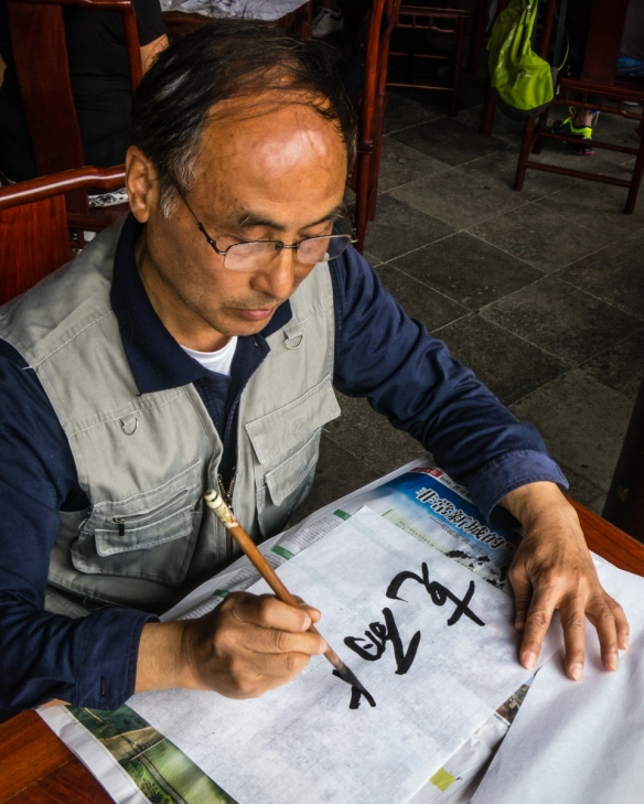 Our calligraphy instructor showing us the Chinese characters for one of our English names, The Garden of Cultivation, Suzhou, China
