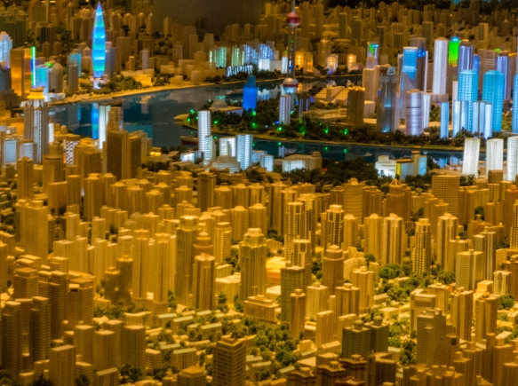 This view of the scale model of the city shows the density of high rise building in the central business district in the foreground; the Bund is on the riverbank at the center-left edge