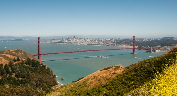 A magnificent vista of the Golden Gate Bridge and San Francisco behind her and the East Bay cities in the distance as seen from atop the Marin Headlands at Fort Baker; San Francisco Bay,
