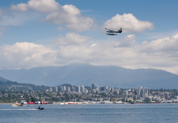 A seaplane is visible flying toward North Vancouver from our vantage point on the Seawall walk on the east side of Stanley Park, Vancouver, British Columbia, Canada