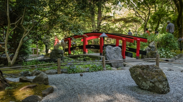 A small Japanese rock garden and a brightly painted bridge over a small stream are typical elements found in the Japanese Garden at The Butchart Gardens, Victoria, British Columbia, Cana