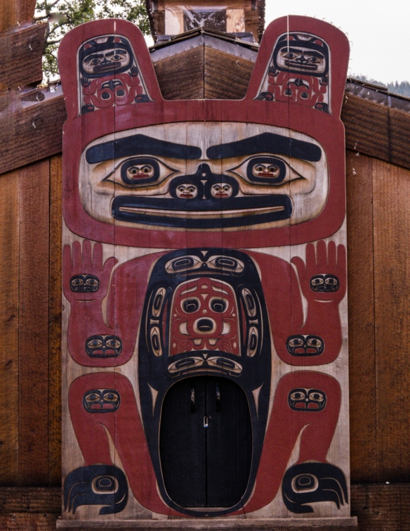A Tlingit decoration at the front of the tribal house on Chief Shakes Island, Wrangell, Alaska; behind the tribal house are preserved (lying down, under shelters) several old Tlingit tot