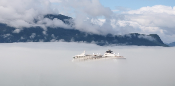 "As we climbed the hills of Wrangell, Alaska, we looked back and discovered that our ship had been nearly ""swallowed up"" by the dense sea fog in the harbor"