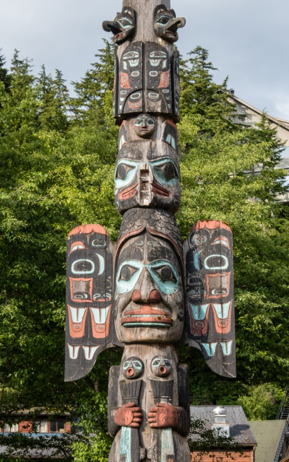 Fog Woman at the lower portion of the Chief Johnson Totem Pole is topped by Raven (replica totem pole raised in 1989), Ketchikan, Alaska, USA
