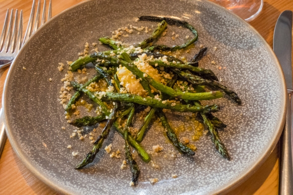 Grilled asparagus with egg yolk (sous vide), fresh pressed soy oil, crunchy millet, Olo, Victoria, British Columbia, Canada; sous vide is a method of cooking in which food is vacuum-seal