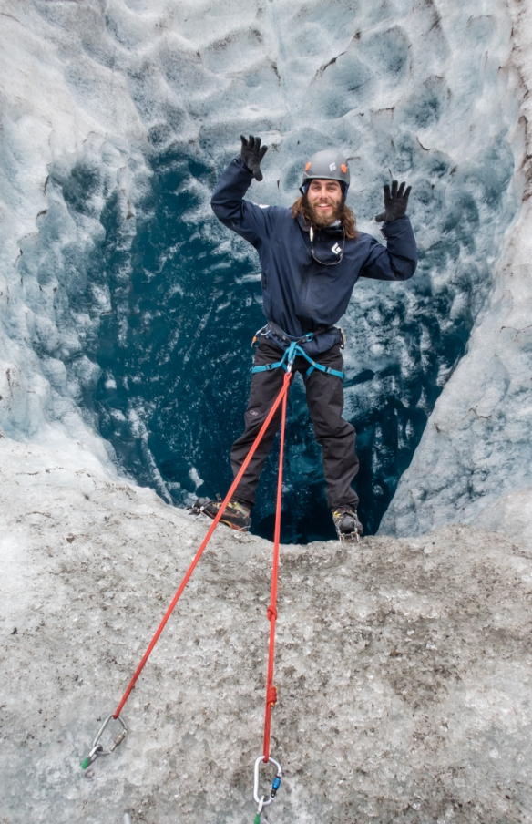 Our guide, Blake, hanging over a tremendously deep Moulin on the surface of Mendenhall Glacier, Juneau, Alaska, USA; many in our group, one at a time, put on a harness and took a turn at