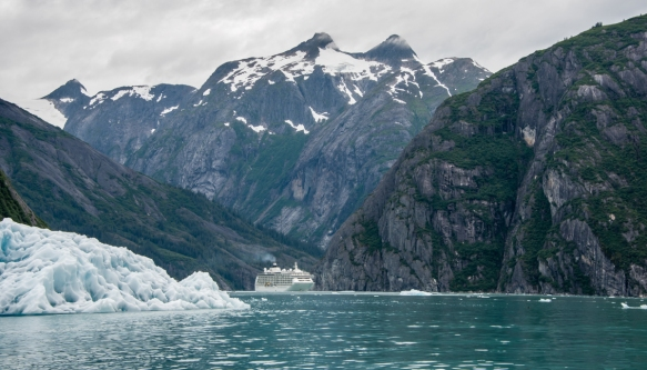 Our ship, almost hiding behind a large iceberg floating in Tracy Arm Fjord, Juneau, Alaska