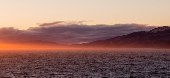 Quite unusual for late June, only a few whispers of fog were drifting in at sunset towards the Golden Gate Bridge, San Francisco, CA, USA; normally the Golden Gate is completely hidden i