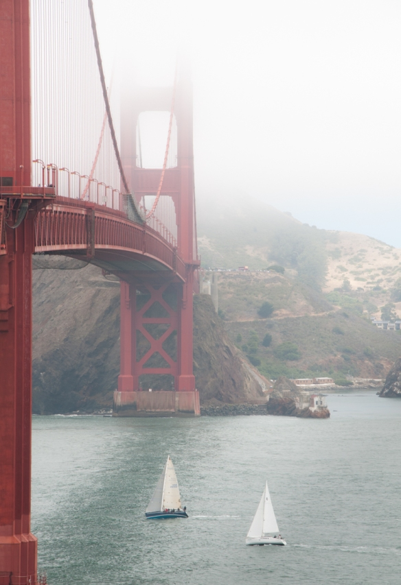 Sailboats heading under the deck of the Golden Gate Bridge, San Francisco, CA, USA, in strong summer winds with the fog swirling around the bridge