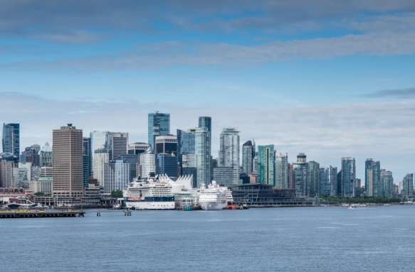 The downtown skyline of Vancouver, British Columbia, Canada, with Canada Place and the Passenger Cruise Terminal in the left center on the waterfront, viewed from Burrard Inlet