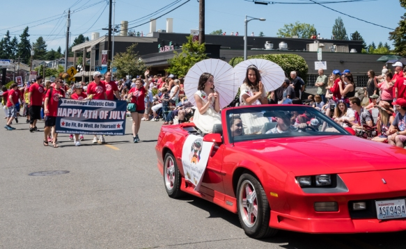 """The """"queens"""" of the local strawberry festival were early participants in the mile-long hometown parade, Grand Old 4th on Bainbridge Island, Washington, USA"""
