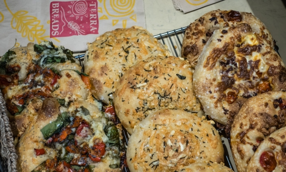 "We tasted one of Terra Breads_ savory ""flatbreads"" which was excellent – the day we visited they were selling roasted red pepper + spinach focaccia, cheese + herb focaccia and bl"