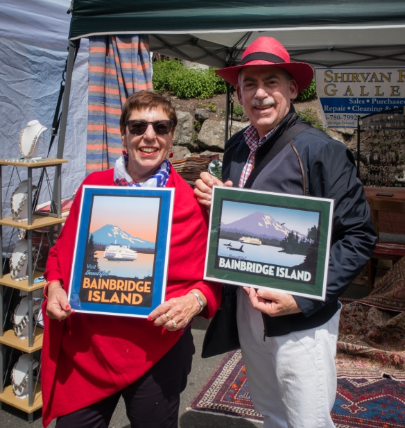 Your intrepid explorer and blogger with posters for sale at the street fair of the Grand Old 4th celebration on Bainbridge Island, Washington, USA_