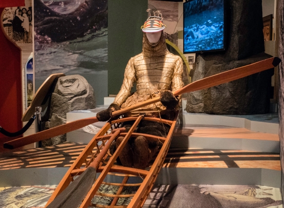 A full-size model of an Unangan (Aleut) kayak with a modern replica of a paddle and hunting visor; the man is wearing a waterproof kamleika; Museum of the Aleutians, Dutch Harbor, Amakna