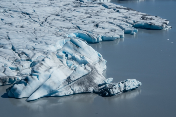 Part of the tidewater edge of Knik Glacier, Anchorage, Alaska USA; note that along the edge there are 400-foot (120 meter) ice walls that rise out of Lake George that is filled with iceb