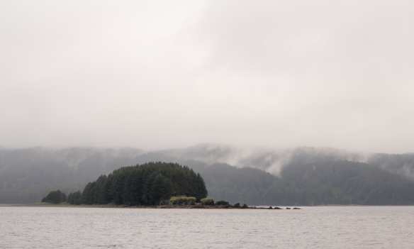 Parts of Kodiak Island were barely visible in the fog, mist and rain; fishing on U-Rascal from Kodiak Island, Alaska USA