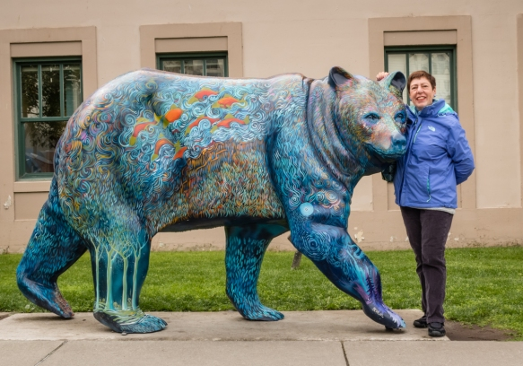 The intrepid explorer nose-to-nose with an artist_s sculpted and brightly painted Alaskan bear in front of City Hall, Anchorage, Alaska, USA