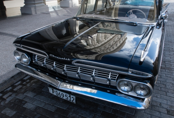 A beautiful 1950s black Chevrolet, restored by Nostalgicar Cuba, parked in front of the Gran Hotel Manzana Kempinski with a reflection of the hotel_s façade on the hood, Havana, Cuba