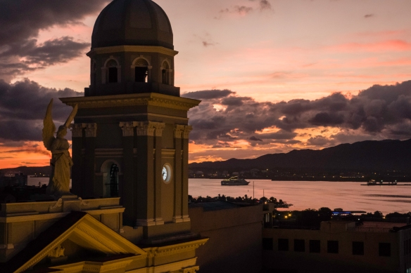 A statue and one of the Cathedral_s two Neoclassical towers at dusk, overlooking Bahia de Santiago de Cuba, Santiago de Cuba, Cuba