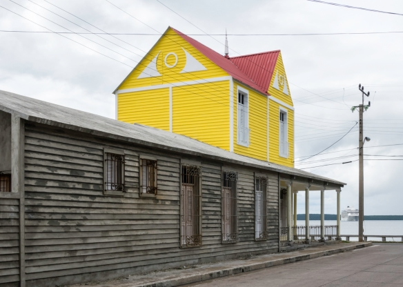 A strikingly colorful restored section of a home in Punta Gorda, Cienfuegos, Cuba, with our ship at anchor in the bay