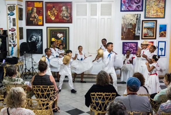 A view of local children performing in a dance recital in an art gallery, as seen by the parents in the audience, Cienfuegos, Cuba