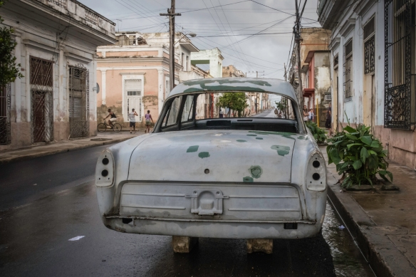 """An old """"classic"""" car, awaiting parts and labor for restoration, sitting on """"blocks"""" on a neighborhood street in Cienfuegos, Cuba"""