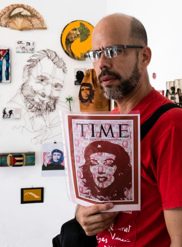 Local artist Adrian Rumbaut holding his original Time magazine cover featuring historic Cubans, in front of his wall collage at the Galería de Arte, Cienfuegos, Cuba