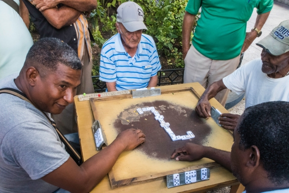 Local men playing dominoes in a park in downtown Santiago de Cuba, Cuba