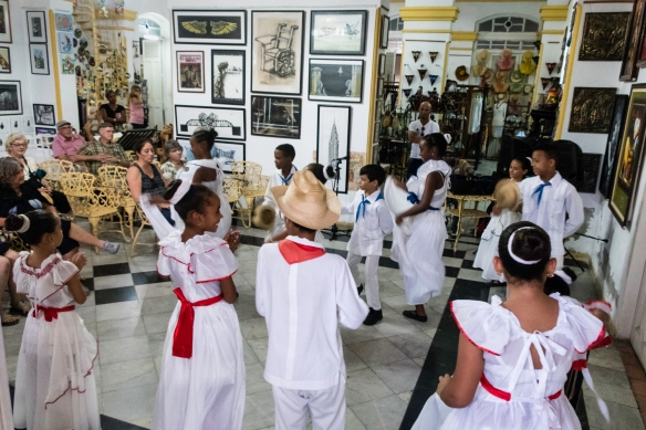 Looking through the street window at local children performing in a dance recital in an art gallery adjacent to the Parque José Martí in the Central Zone of Cienfuegos, Cuba