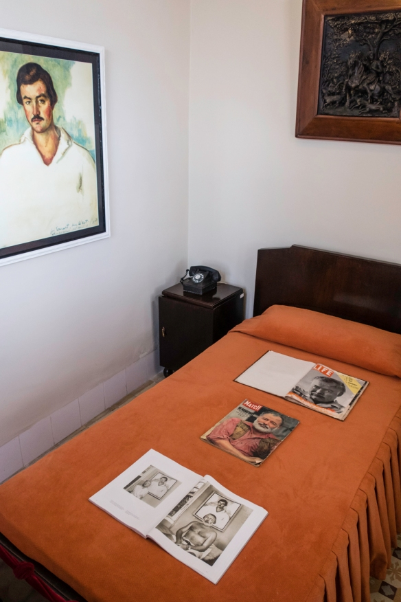 Published magazine covers with Hemingway on the cover, along with Hemingway photographs – on his bed in his room during 1939 in the Hotel Ambos Mundos in Havana, Cuba