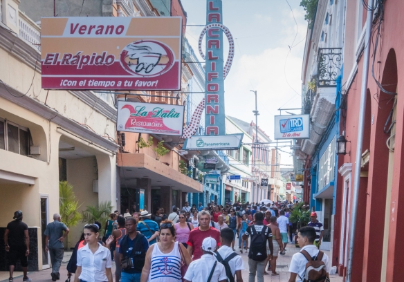 Shoppers on a weekday walking down the main shopping street in Santiago de Cuba, Cuba