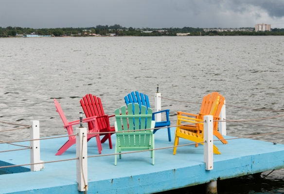 "With a thunderstorm approaching, the brightly painted ""Adirondack-style"" chairs on the dock adjacent to the restaurant were empty, luncheon at El Lagarto, Cienfuegos, Cuba"