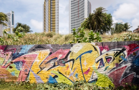 Street art (graffiti) on a retaining wall, with the downtown high rises of Natal, Brazil visible behind Praia de Ponta Negra (Ponta Negra Beach)