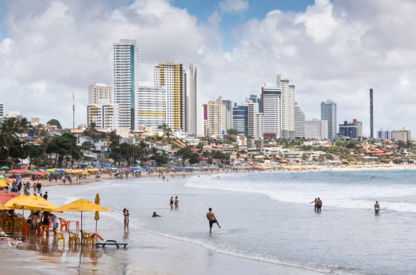 The skyline of the city of Natal, Brazil is visible behind Praia de Ponta Negra (Ponta Negra Beach)