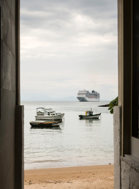 Viewed through an alleyway between two shops, the large MSC cruise liner (3,000 passenger capacity) dwarfs the local fishing boats which here resemble the bathtub toys our grandchildren
