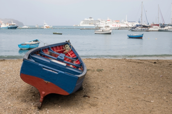 Behind the fishing boat on the beach is our ship (on the horizon), docked in Mindelo, São Vicente, Cape Verde (Cabo Verde)
