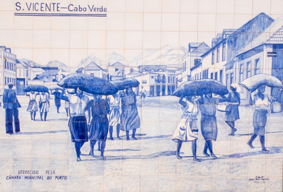 Local Art in Mindelo, São Vicente, Cape Verde (Cabo Verde) -- blue-and–white ceramic azulejos historic mural #3 – an historical depiction of barefoot women slaves carrying 100 poun