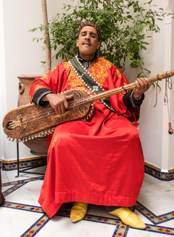 A local musician playing a traditional Moroccan stringed instrument at our luncheon from our cooking class at La Maison Arabe, Marrakech, Morocco