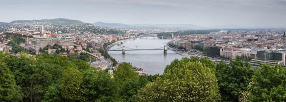 A panorama of Budapest, the capital of Hungary, with the Chain Bridge crossing the Danube River in the foreground; the hilly Buda district is on the left and the flat Pest district (wher