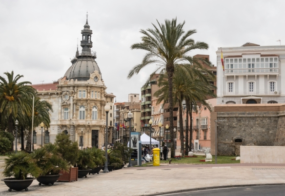 A view from the port, through palm trees, of the Plaza a de Héroes del Cavite, the corner of city hall and the entrance to Casco Antiguo (Old Quarter) in Cartagena, Spain
