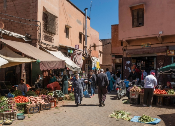 Outdoor stalls selling fresh fruits and vegetables just outside on of the covered souks in Marrakech, Morocco
