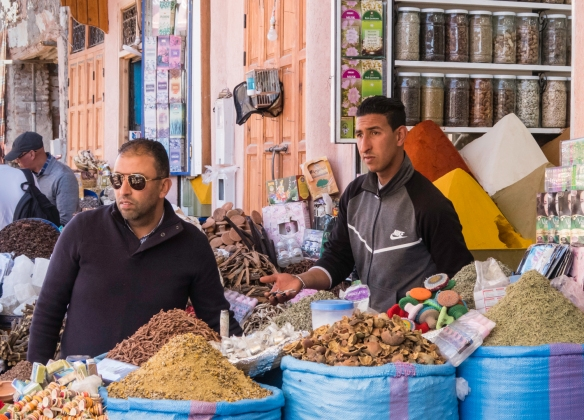 Spice sellers negotiating with a customer in a souk, Marrakech, Morocco