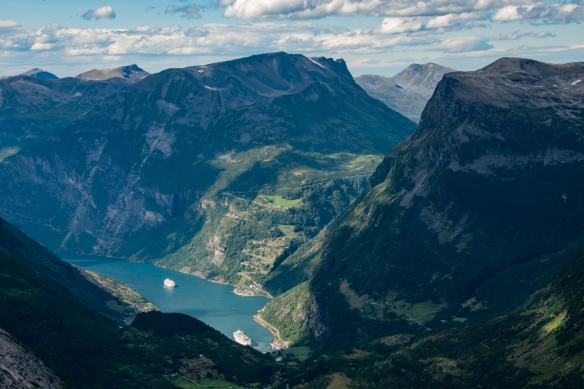 A close up of Geirangerfjord and the small village of Geiranger, Norway (tucked under the mountains and only partially visible, with the Ørnesvegen (Eagle_s Road), featuring 11 hairpi