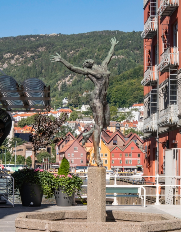 A contemporary statue celebrating life on the quay on the western side of the inner harbor (Vågen Harbor) of Bergen, Norway; across the harbor are the Bryggen gabled, wooden warehouses