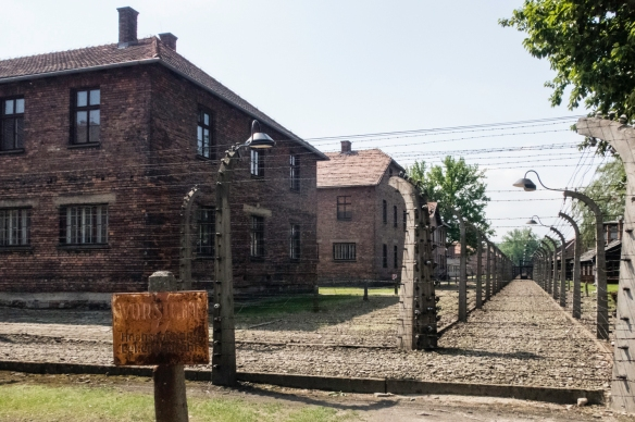 A corner view of the barbed-wire protected barracks at Auschwitz, Oświęcim, Poland, as seen from outside (near the location of the crematorium in the photo above)